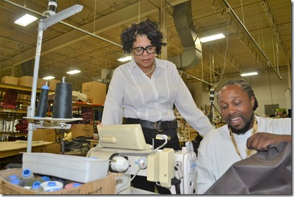 M3Development Group President Melissa Posey  (left) watches as Abin Lee Lowman, a former federal prison inmate who she placed at Snoozer Pet Products, sews at the plant in Piedmont. (Photo by Bill Poovey)