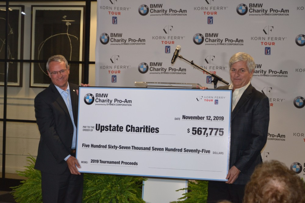 Max Metcalf, left, and Bob Stegner unveil and present a check representing the funds to be divided among four charities from the 2019 tournament. (Photo/Ross Norton)