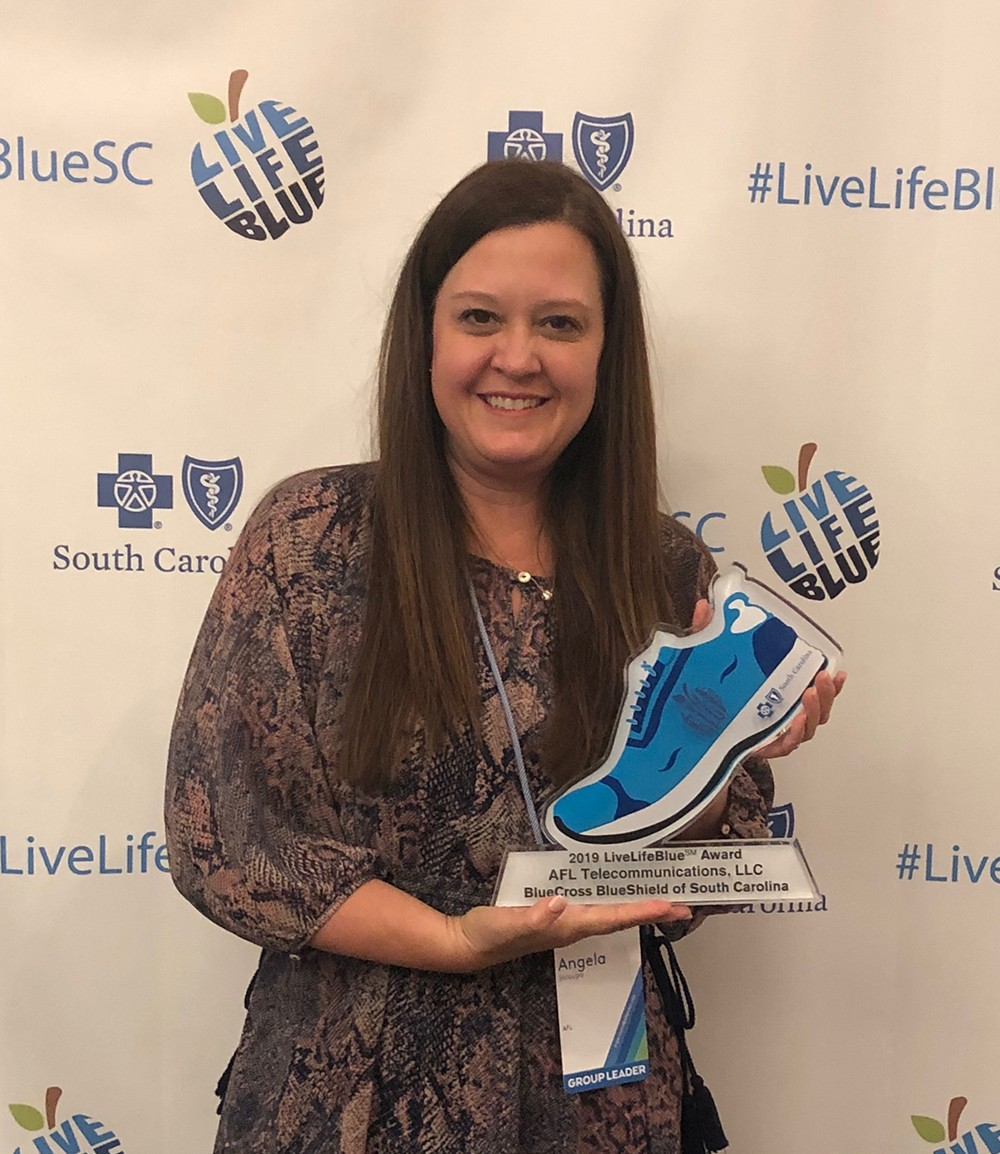 Angie Myers, benefits and wellness director for AFL, accepts the Blue Shoe award for the company. (Photo/Provided)