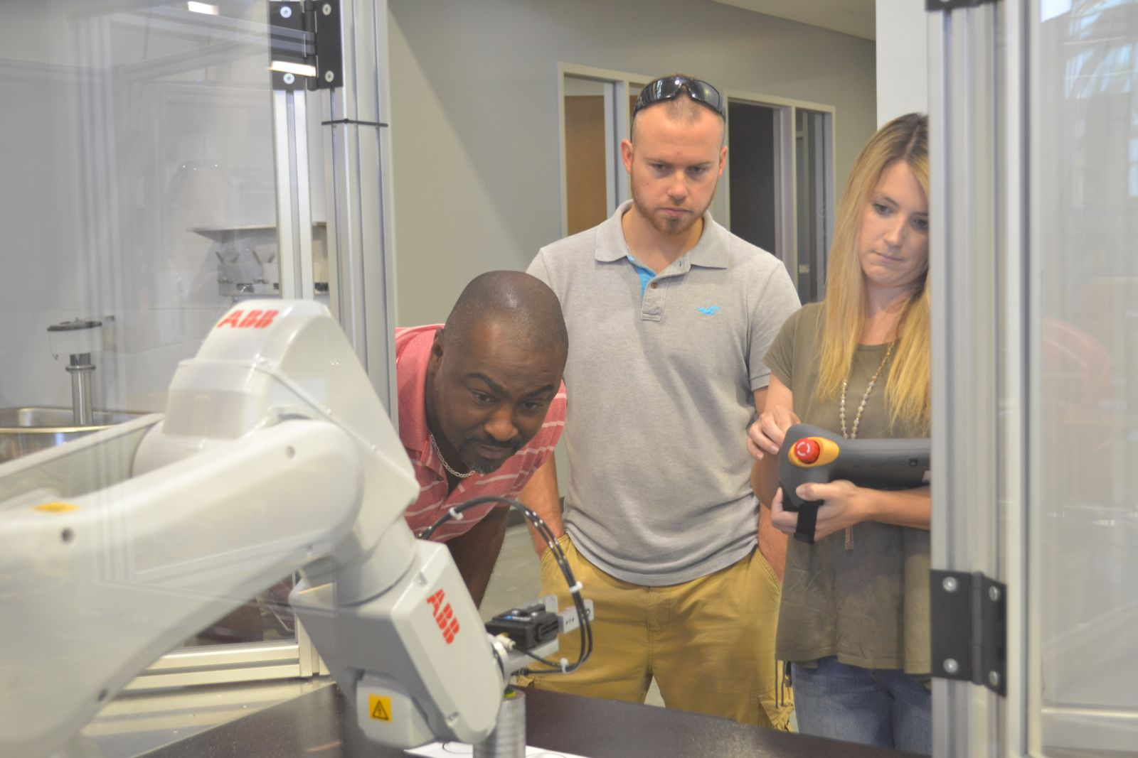 Rodney Jones, academic program director of mechatronics at Greenville Tech, left, and students Brandon Gillespie and Ashley Edmond maneuver the arm on an ABB robot at the Center for Manufacturing Innovation. (Photo by Teresa Cutlip)
