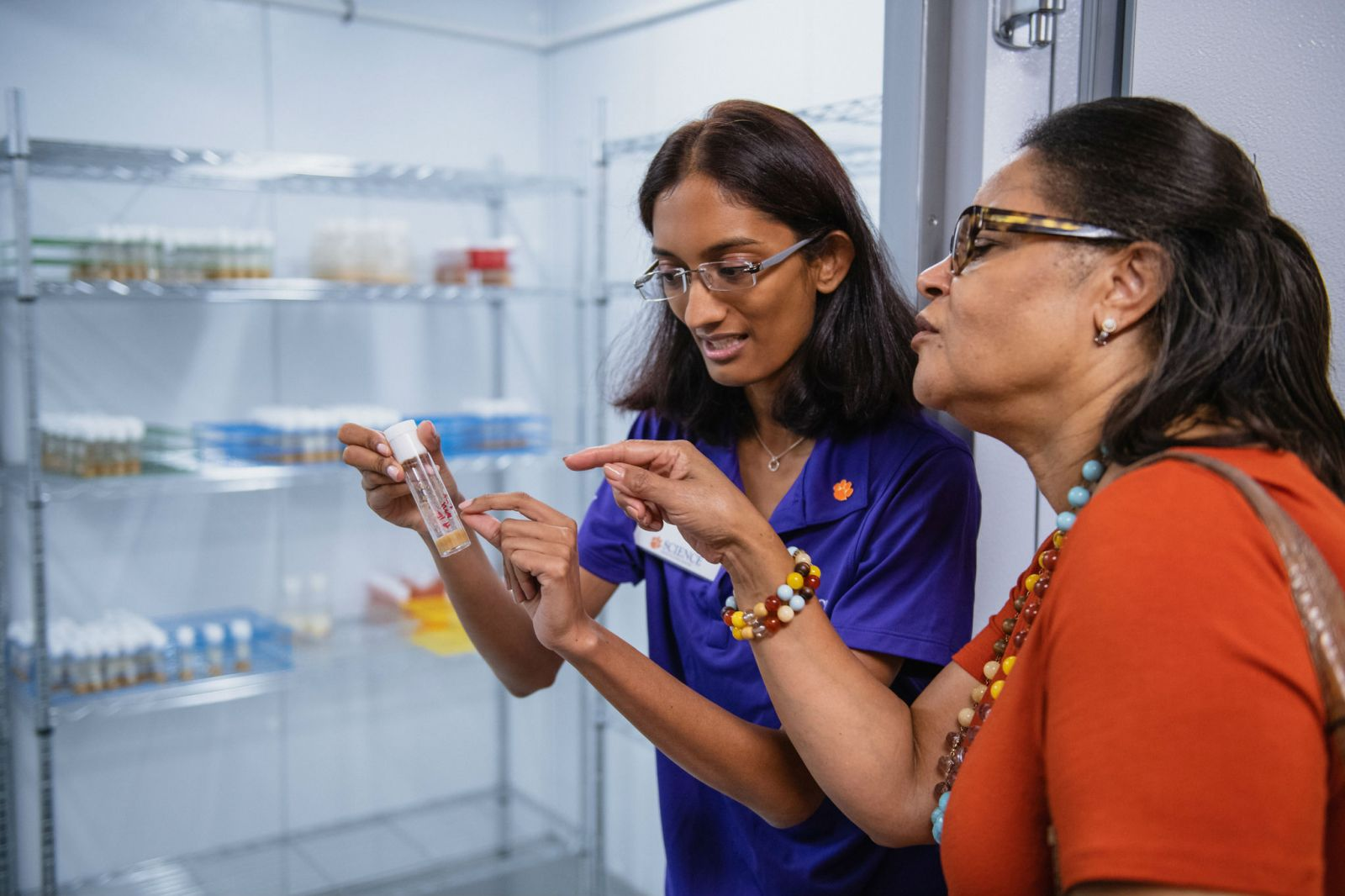 Doctoral student Sneha Mokashi (left) shows a sample to a guest at the opening of the Clemson Human Genetics Center. (Photo/Provided)