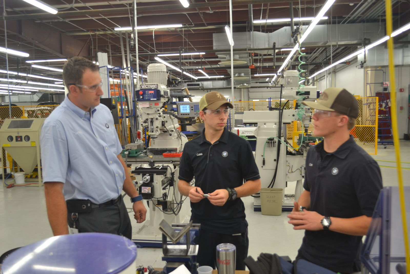 Dmitry Kopytin, left, gets a project update from BMW Scholars Caleb Nelson and Cole Johnson. (Photo by Teresa Cutlip)