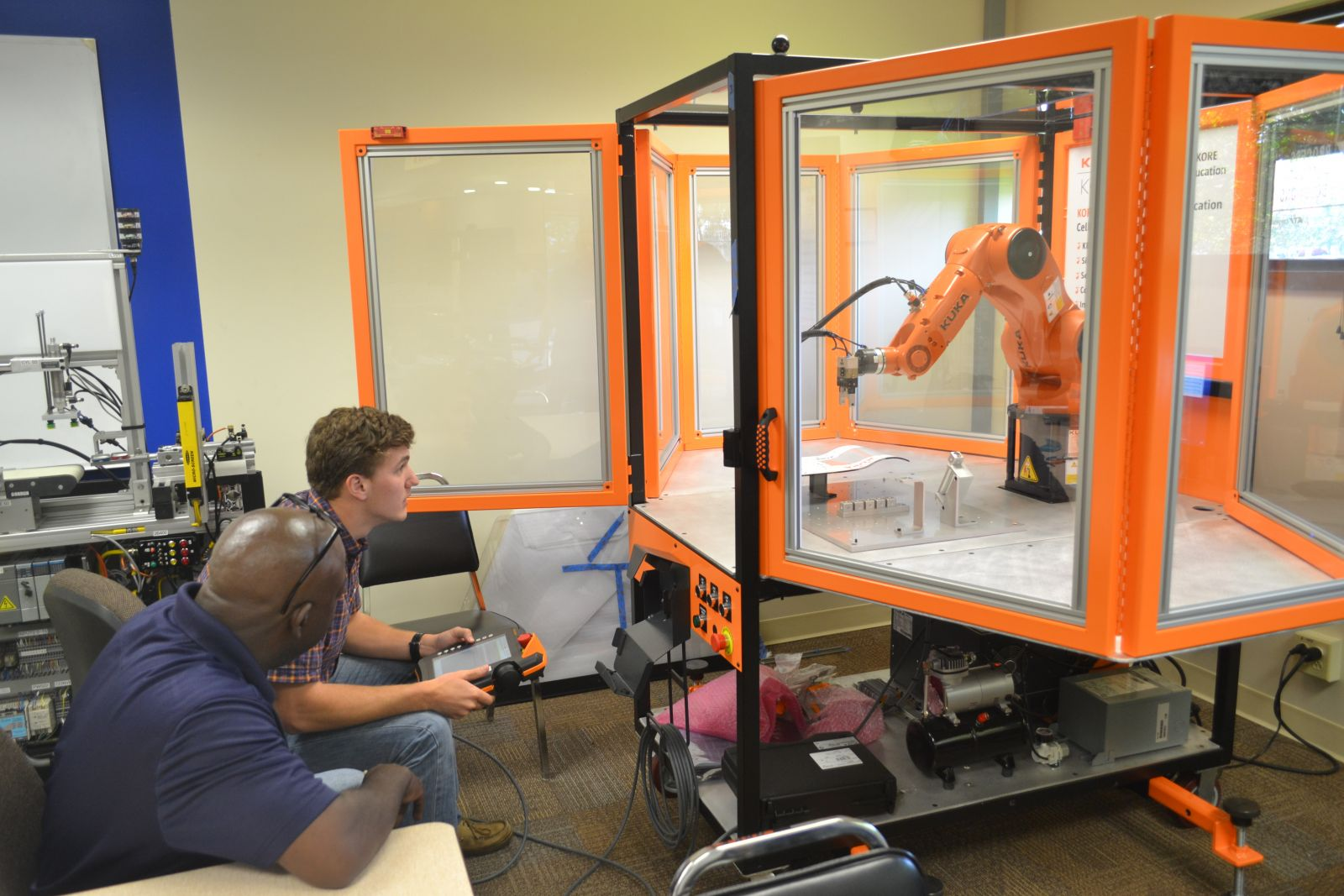 PA Solutions employees, from left, William Lloyd and Keaton Walker, train on the Kuka industrial robot that will be incorporated into classes at ECPI University Greenville. (Photo by Teresa Cutlip)