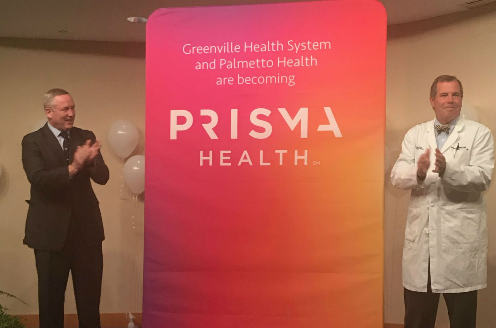 Prisma Health co-CEO Michael Riordan, left, and Dr. Spence Taylor, president of the Upstate affiliate of Prisma Health, unveil the company's new logo. (Photo/Teresa Cutlip)